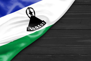 Flag of Lesotho and place for text on a dark wooden background
