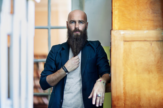 Portrait of bearded thoughtful man strokes beard