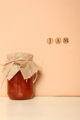 A jam can near the wall on which is written the word honey