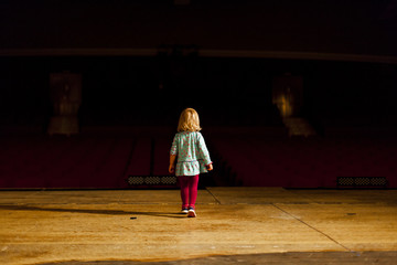 Kleines Kind auf Theaterbühne schaut richtung Tribühne. Little child on theatre stage looking to audience.