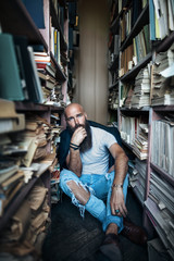Upset hipster man sitting on floor in library