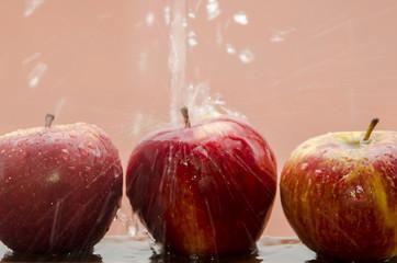 Tres manzanas mojándose sobre fondo rojo