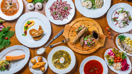 Assorted dishes borsch, sorrel soup, lamb kebab, Fried salmon, meat Solyanka, herring with potatoes