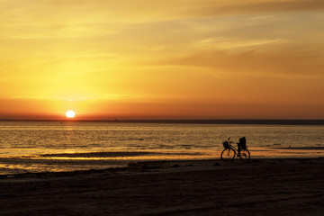Beautiful sunset over the sea. The sky is painted with bright colors. Bicycle near the water. Summer evening. Sunset beach.  Gulf of Finland, Baltic sea, Sestroretsk, Saint-Petersburg, Russia