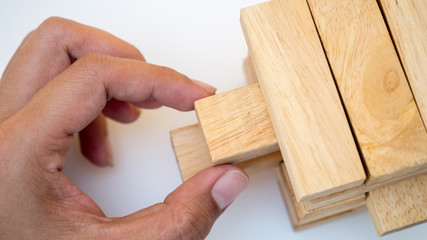 Closeup hand man take one block on The tower from wooden blocks, white tone
