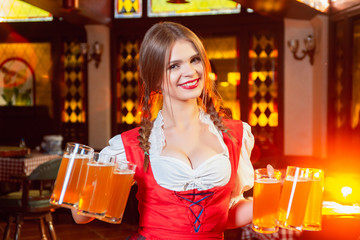 Young beautiful girl holds six mugs of beer in hands at celebration of oktoberfest. Beer glasses on the background of the female breast.