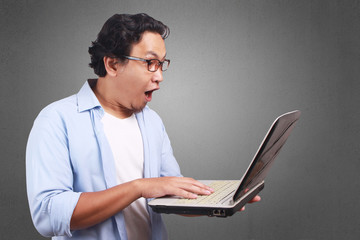 Young Man Playing with His Laptop, Surprised Expression