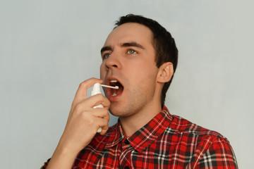 The sick man treats the throat spray medicine spray of white spray.