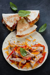 Tortilla bread with roasted chicken, vegetables and cheddar cheese for making quesadilla, high angle view