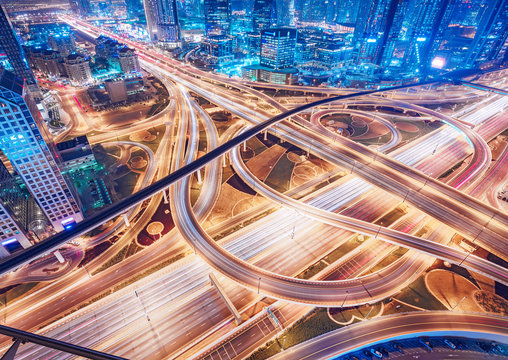 Aerial view of big highway interchange with traffic in Dubai, UAE, at night. Scenic cityscape. Colorful transportation, communications and driving background.
