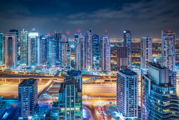 Scenic nighttime skyline of big modern city. Aerial view on skyscrapers and highways of Dubai Marina, UAE. Multicolored travel background.