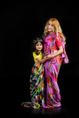 A small child and his mother in traditional Indian attire.