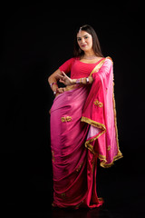 The girl, dressed in a Sari of Indian culture.
