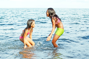 Two happy young girls playing with the water in the sea