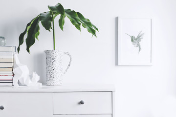 Stylish and modern white interior with mock up frame , cat figures, stand of books and tropical leaf. White and minimalistic concept of cupboard shelf.