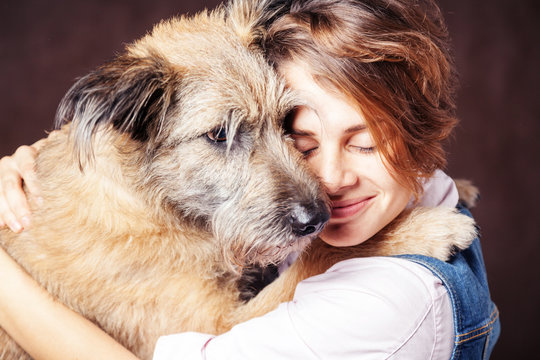 Beautiful young woman with a funny shaggy dog on a dark background. Love, care, friendship