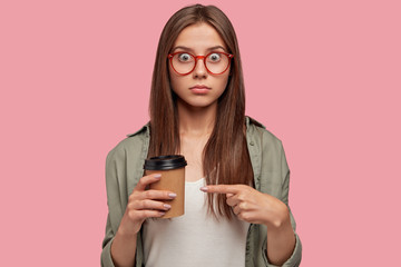 I need badly this! Isolated shot of stunned student in eyewear, indicates at disposable cup with beverage has surprised expression, dressed in fashionable outfit. People, drinking and coffe break