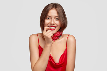 Image of rejoiced young female flirts with boyfriend, has broad smile, white teeth, bites finger, wears red dress and stylish bandana, has dark hair, healthy skin, isolated over white background.