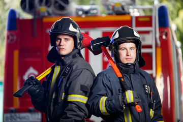 Photo of two firemen men in camera with axes in hands near fire engine