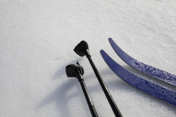Blue skis and ski poles on top of the snow in Finland.