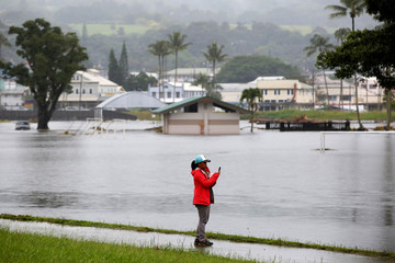 Rose Badua, of Keaau, takes pictures of flooding caused by Hurricane Lane in Hilo