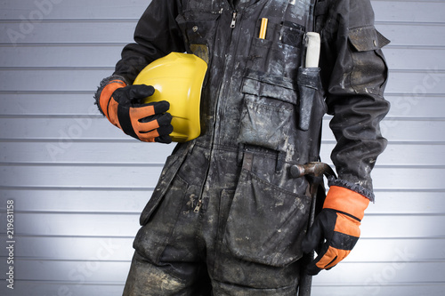 construction worker in dirty overalls in finland the laborer have orange gloves yellow helmet
