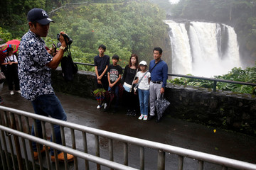 Tour guide Shawn Igarashi takes pictures of his clients in front of a waterfall swollen by rain from Hurricane Lane in Hilo
