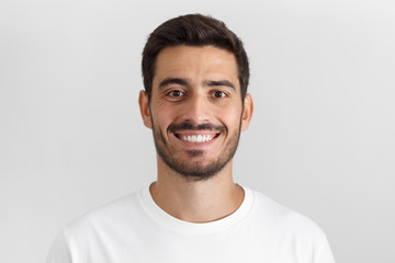 Close up portrait of smiling attractive man in white t-shirt isolated on gray background