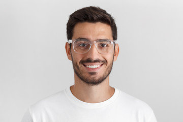 Close up daylight shot of smiling bearded man in white t-shirt and trendy trasparent eyeglasses, isolated on gray background