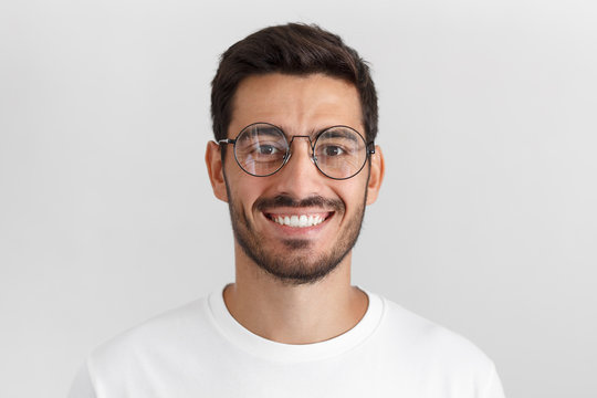 Daylight portrait of young handsome caucasian man isolated on grey background, dressed in white t-shirt and round eyeglasses, looking at camera and smiling positively