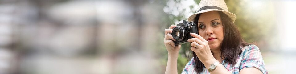 Beautiful young woman taking pictures in a park