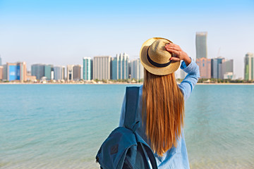 Woman with backpack weaing the hat. On the background is panorama of Abu Dhabi
