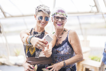 hippy couple of caucasian beautiful females use a smart phone. Different ages  nice attractive people stay together in happy leisure activity with friendship. Sharing content on social for cheerful