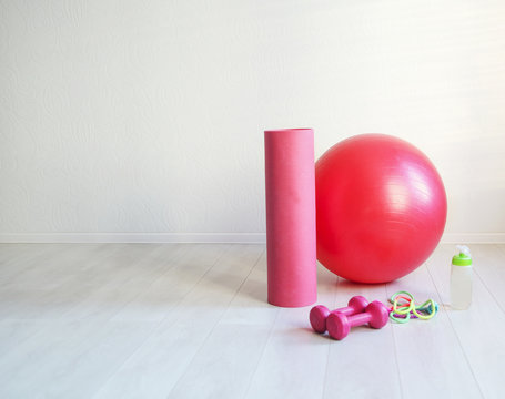 Gym ball, yoga mat, skipping rope, dumbbell  and bottle of the water closeup on white background