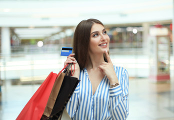 Shopper girl holding credit card and shopping bags looking up.