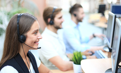 Attractive positive young businesspeople and colleagues in a call center office.