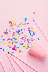Drinking Paper Cup Striped Straws Colorful Confetti Scattered on Fuchsia Background. Flat Lay Composition. Birthday Party Celebration Kids Fun Cheerful Atmosphere. Greeting Card Poster Template