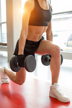 close up dumbbell lunge blonde woman with earphones workout exercise at gym, one leg split squats