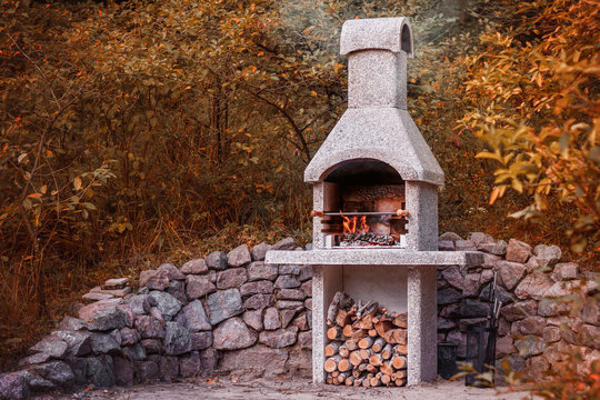 Stone garden oven for grill or barbeque is in a backyard at autumn season