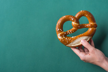 Young woman hold in hand German savory lye pretzel with salt on dark green background. Poster Banner for Bakery Coffee Shop Menu. Oktoberfest Card. Copy Space