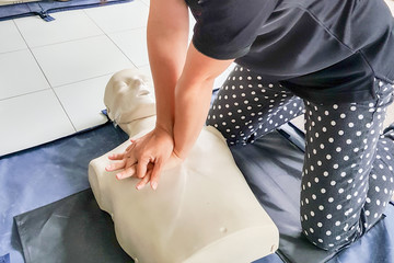 Cardiopulmonary resuscitation ( CPR ) training concept.Blur background woman student using hands doing heart pump in basic life saving and support course.