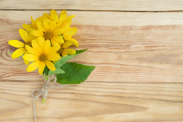 bouquet of yellow daisies close-up on rustic wooden table background.
