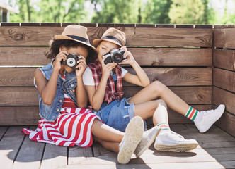 Beautiful little girls taking pictures with photocameras. Cute smilling happy girls playing outdoors