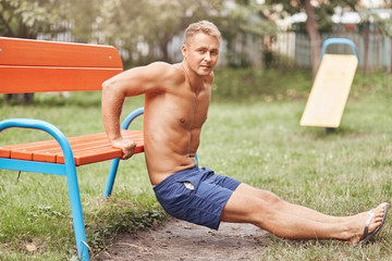 Determined bodybuilder works on his body shape, does push ups with help of bench, wears shorts, has sport training in park, looks at camera. Strong athletic sportsman goes in for sport outdoor