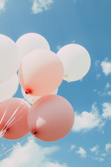 White pink balloons against the sky. Sky with clouds