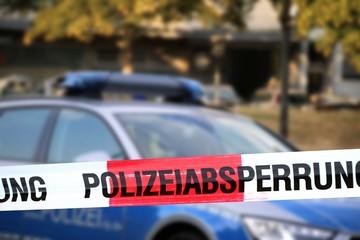 Polizeiabsperrung mit Polizeiauto im Hintergrund