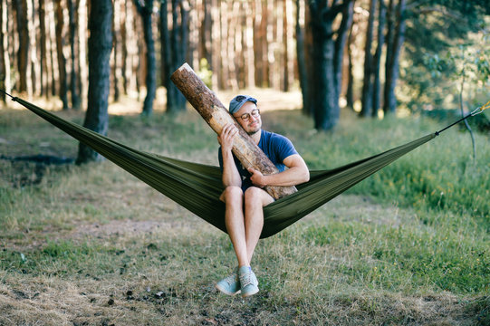 Odd weird strange unusual male person. Outlandish funny crazy foolish man sleeping in hammock with huge wooden log at nature among trees.  Wood and forest lover. With beam in bed.  Leisure lifestyle.
