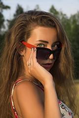 Close up portrait of beautiful young girl with long hair and sun glasses. Romantic female image.