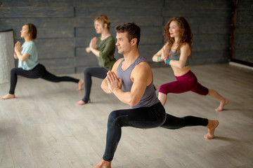 Young people doing flexibility exercise, class of body balance, yoga practice indoors over grey studio background, sportive man in Warrior pose standing on foreground.