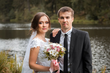 Happy wedding couple. Bride and groom are embracing in the park against the background of the pond. Sunny autumn day